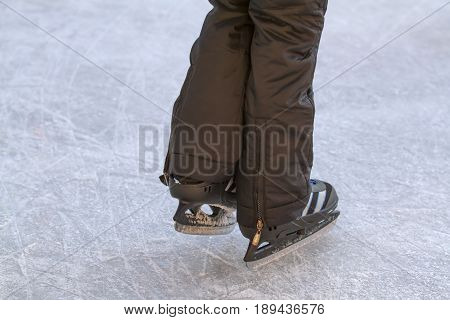 Child legs on an ice rink in detail