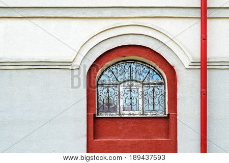 White plaster facade with red arched window and red downspout