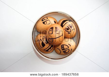 Eggs with painted face. Photo for your design. Eggs float in a plate. To come off to the fullest. Joy and relaxation. Holiday together
