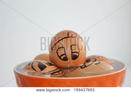 Eggs with painted face. Photo for your design. Egg to swim in a bowl. To come off to the fullest. Joy and relaxation. Vacation