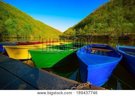 Colorful vivid fishing boats on lake Hamori in Lillafured, Hungary, outdoor travel background