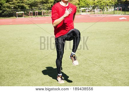 A sprinter perfoming A-Skips on a green turf field warming up for track and field practice