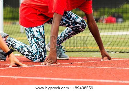 High school girls practicing the start of a track sprint race in the