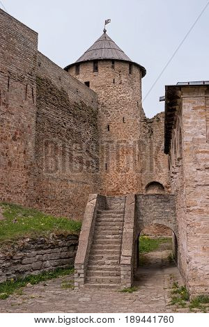 Russian medieval castle in Ivangorod. Located opposite the Estonian city of Narva, not far from St. Petersburg. Watchtower and staircase to the Assumption Cathedral. Photographed on a cloudy day.