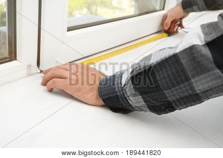 Young man installing window shades at home