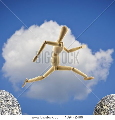 Wooden mannequin is jumping over the abyss at cloudy sky background. Big jump concept.