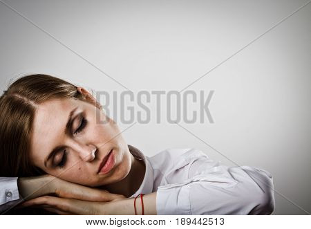 Tired young woman in white is sleeping.