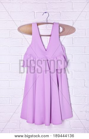 Hanger with beautiful lilac dress on brick wall background