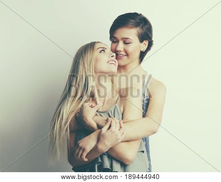 Young lesbian couple on light background
