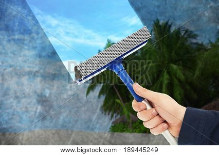 Man removing dirt from glass with squeegee. View of blue sky through window. Cleaning service concept