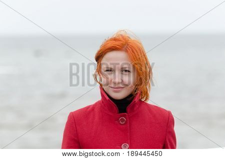 Portrait of a beautiful red girl on a cold windy day