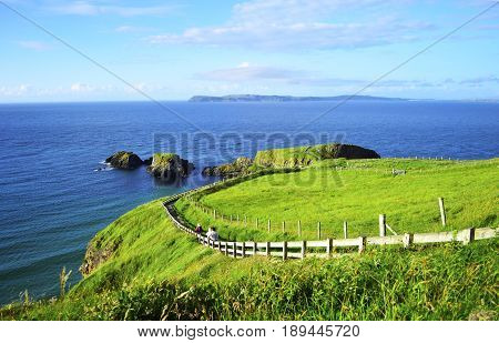 People Walking Along the Coastline Footpath to Carrick-a-Rede Rope Bridge Giant's Causeway Northern Ireland.