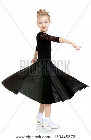 The slender little blonde girl dancer in the long dress of black color made specifically for performing .The girl gracefully spinning , the edges of her dress fluttering in the wind.Isolated .