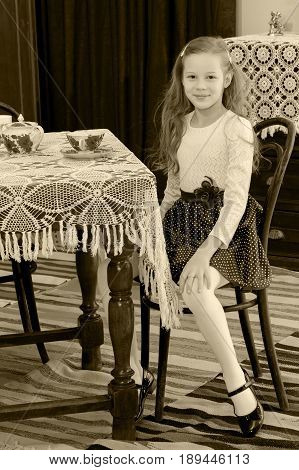 Cute little girl drinking tea at an antique table with a lace tablecloth.Black-and-white photo. Retro style.
