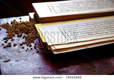 Close up photo of a traditional tibetan prayer book, with seed of grain used during the religion rituals.