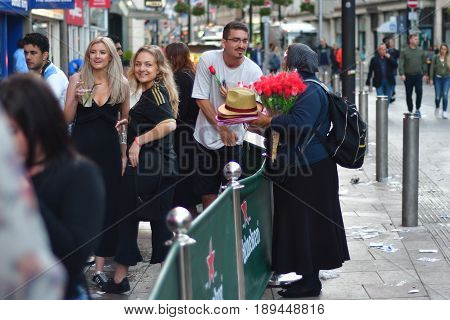 CARDIFF UK - 3 JUNE 2017 Flower seller and partygoers during Champions League Final. British police and security services on high alert as hundreds of thousands of fans enjoy football in the capital of Wales
