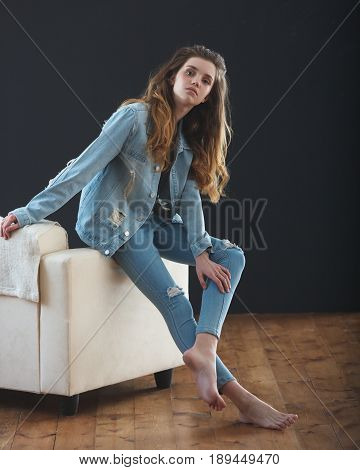 young teenage girl wearing ripped jeans jacket , portrait over dark background