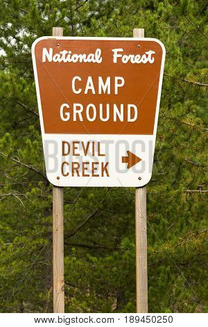 A metal sign along the highway points the way to Devil Creek Campground