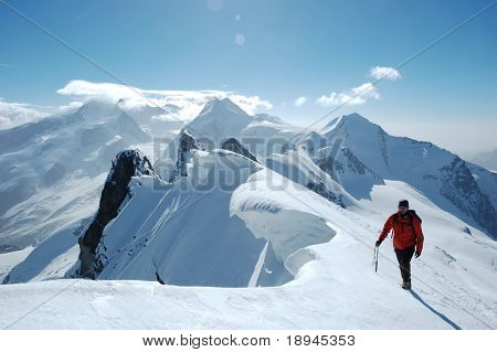 Climber on background the peaks and glaciers of Monte Rosa massif, west Alps, Europe