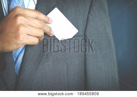 Young businessman holding white business card and who takes out blank business card from the pocket of his suit.