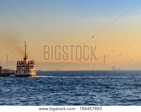 Ferryboat in the bosphorous sea during sunrise with bogazici bridge background
