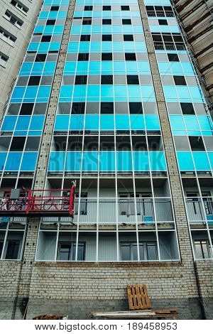 Construction of a modern multi-storey residential building. Glass balconies are blue.
