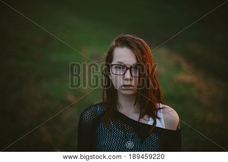 A sad portrait of a red-haired girl in nature at sunset.
