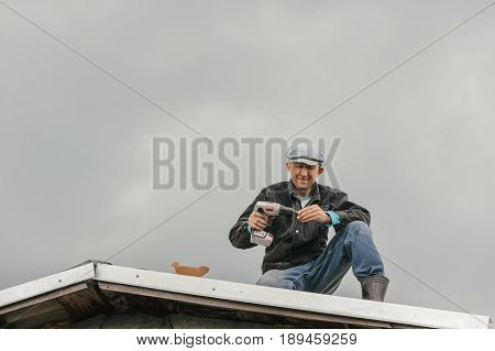 A man in work clothes tighten screws with a screwdriver on the roof against a cloudy sky.