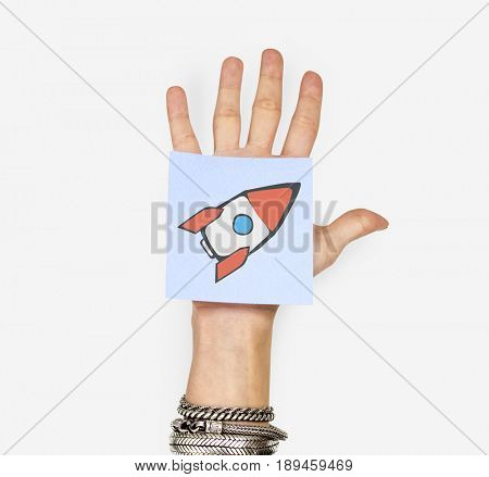 Hand holding note with rocket start up icon