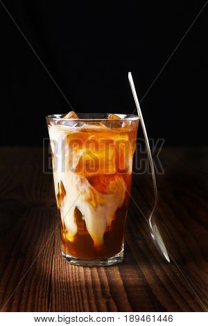 Closeup of a glass of iced coffee on a dark wood table. Fresh poured cream is permeating through the glass and a spoon is leaning on the glass. Vertical shot on a black background with copy space.