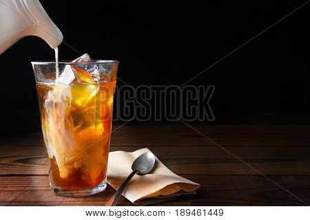 Closeup of a glass of iced coffee on a dark wood table. Fresh pouring cream is permeating through the glass with a spoon and napkin next to the glass. Horizontal on a black background with copy space.