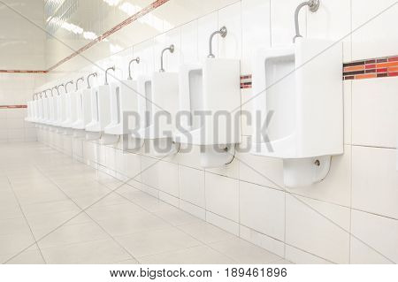 Wall and floor tiles white bathroom. Public toilets urinals