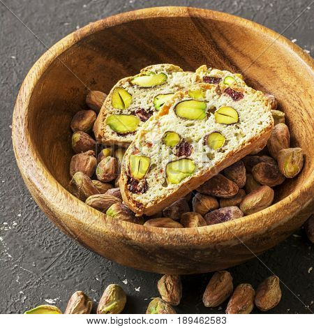 Traditional crispy Italian biscotti or cantuchini crackers with pistachios and dried cranberries in a bowl of olve wood on a dark background. Home classic healthy food
