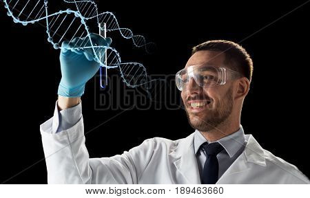 science, genetics and people concept - young smiling scientist in safety glasses with test tube and dna molecule projection over black background