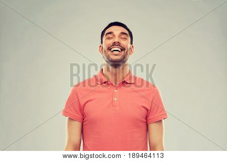 emotion and people concept - laughing man in polo t-shirt over gray background