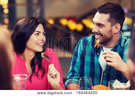 leisure, food and drinks, people and holidays concept - happy couple with friends having dinner at restaurant
