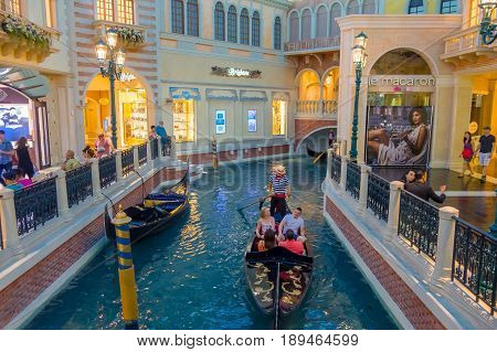 LAS VEGAS, NV - NOVEMBER 21, 2016: An unidentified people walking in the plaza and using the gondola of the Venetian hotel replica of a Grand canal in Las Vegas with more than 4000 suites it s one of the most famous hotels in the world.