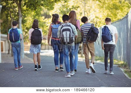 Rear view of school kids walking on road in campus at school