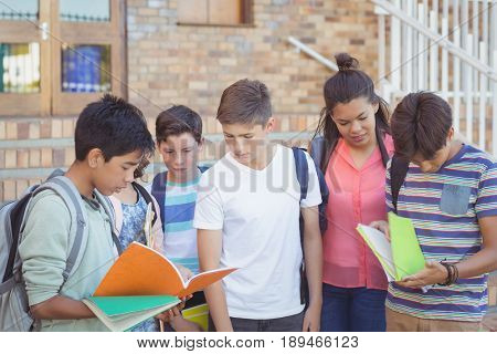 School kids discussing over text book in campus at school