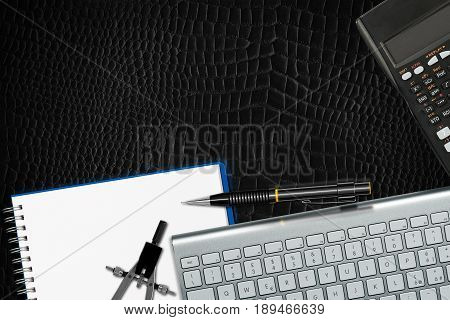 Office desk - top view on a black leather background with copy space