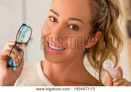 Smiling young blonde woman holding contact lens case on hand and holding in her other hand a blue glasses on blurred background., eyesight and eyecare concept.