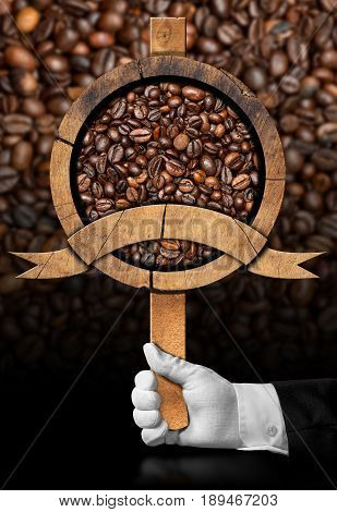 Waiter holding a wooden sign with roasted coffee beans and copy space. On a dark background with many coffee beans