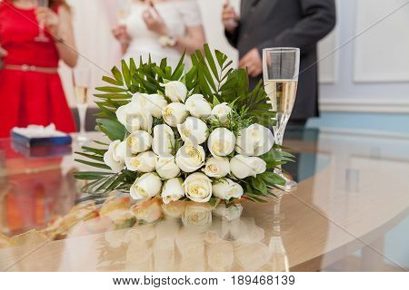 Bride with champagne and flowers bouquet roses