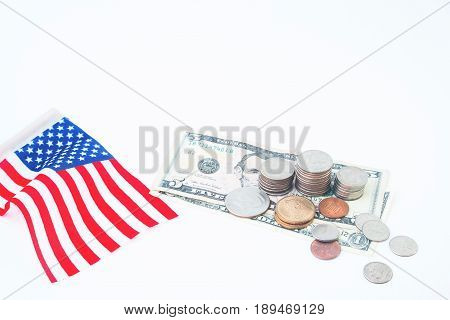 Stack of coins and dollars bill with usa flag on white Business and finacial concept