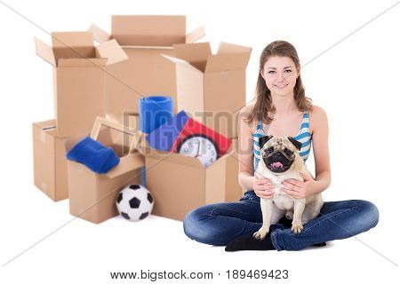 moving day concept - young woman with brown cardboard boxes and cute pug dog isolated on white background