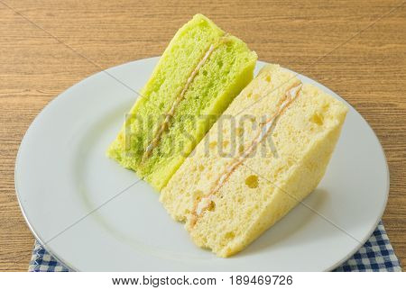 Snack and Dessert Green Pandan and Vanilla Chiffon Cake Made With Butter Eggs Sugar Flour Baking Powder and Flavorings on White Dish.
