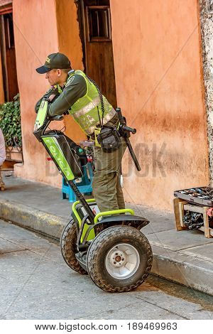 Cartagena, Colombia- March 2, 2017: Police officer patrols the streets in old town Cartagena Colombia