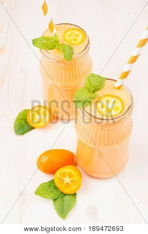Freshly blended orange citrus kumquat fruit smoothie in glass jars with straw mint leaf cute ripe berry close up. White wooden board background vertical.