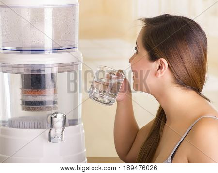 Close up of a beautiful woman drinking a glass of water with a filter system of water purifier on a kitchen background.