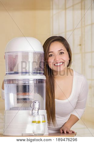 Beautiful woman next to the filter system of water purifier on a kitchen background.